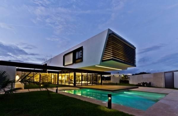 这是由Carrillo Arquitectos y Asociados设计的特默住宅。项目位于墨西哥尤卡坦半岛特默的一片居住区内,住宅坐落于一个梯形用地转角处。场地东边长60米,北边长39米。住宅空间旨在营造出一个没有墙壁分隔的环境,而户外与室内紧紧联系,形成一个单一的环境,突出不同环境中的视线。为了达到这个目的,建筑师提出了L型的平面布局,其中两个走廊围合出一个中央花园,其中一条走廊是服务性功能的,而另一条是服务于生活空间的(包括公共的和私密的)。随后,将一条走廊旋转45度,有助通风,同时将花园景色